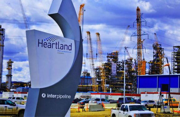 Heartland Petrochemical complex front gate with sign and facility under construction in background