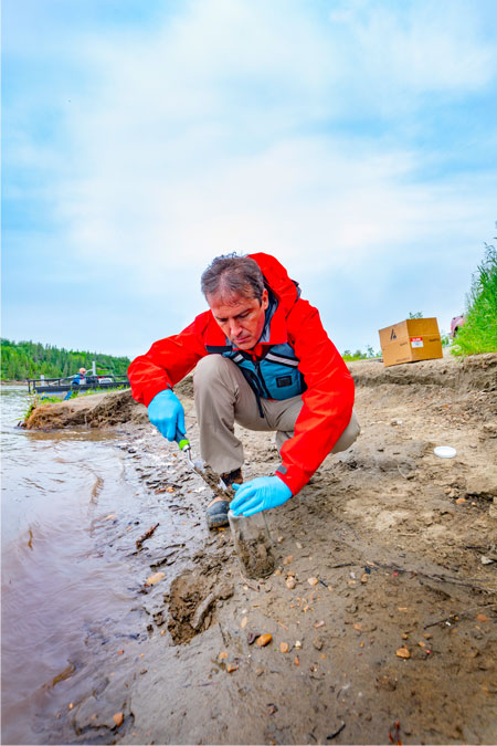 Photo of a scientist collecting samples from a river shoreline